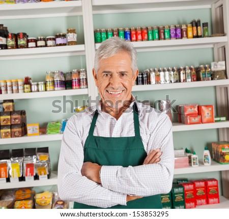 Portrait of confident senior male owner smiling at supermarket - stock photo