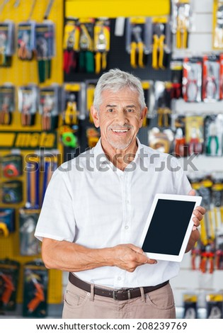 Portrait of confident senior man displaying digital tablet in hardware store