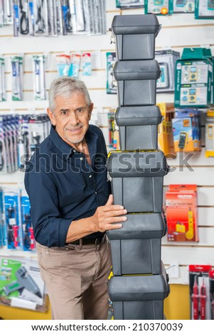 Portrait of confident senior man stacking toolboxes in hardware store