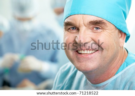 Portrait of confident senior surgeon looking at camera on background of working group - stock photo