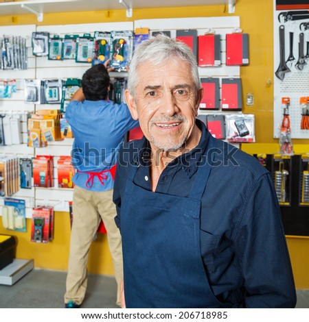 Portrait of confident senior worker smiling with coworker working in background at hardware store - stock photo
