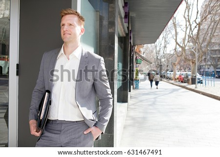 Portrait of confident smart business man carrying folders with paperwork in a financial city street, wearing a suit, sunny outdoors. Professional successful male, business lifestyle, exterior.