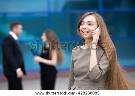 Portrait of confident smiling young woman talking on smartphone outdoors. Happy beautiful caucasian woman using mobile phone, making call on the street in summer with businesspeople on the background - stock photo