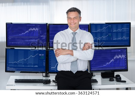 Portrait of confident stock market broker leaning on desk at office