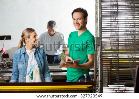 Portrait of confident supervisor holding digital tablet while standing with workers in paper factory