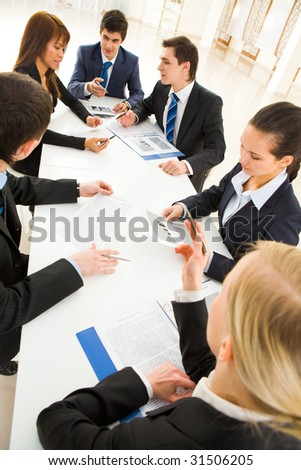 Portrait of confident team discussing documents and interacting with each other at briefing - stock photo