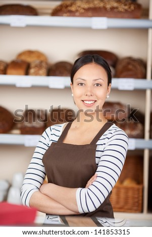 Portrait of confident teenage girl with arms crossed standing at coffeeshop counter - stock photo