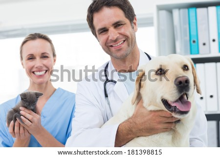 Portrait of confident veterinarians with dog and kitten in hospital - stock photo