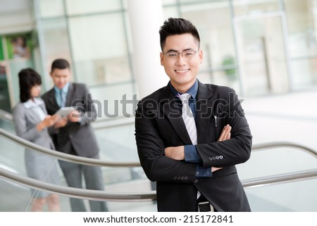 Portrait of confident Vietnamese businessman with his colleagues in background - stock photo