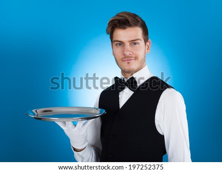 Portrait of confident waiter carrying tray over blue background - stock photo