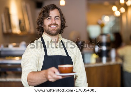 Portrait of confident waiter holding coffee cup while standing in cafe - stock photo