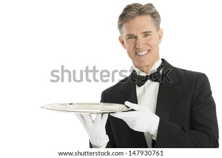 Portrait of confident waiter in tuxedo holding serving tray against white background