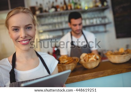 Portrait of confident waitress with digital tablet standing with colleague at cafe - stock photo