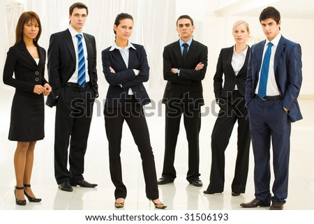 Portrait of confident well-dressed business people standing in semicircle with smart lady in center