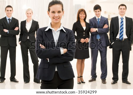 Portrait of confident well-dressed lady with business team at background