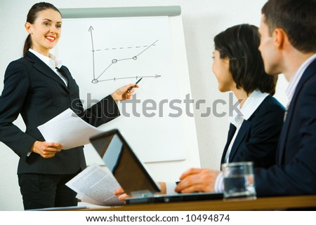 Portrait of confident woman demonstrating her report to colleagues - stock photo
