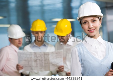 Portrait of confident woman in helmet looking at camera in working environment - stock photo