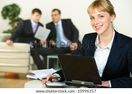 Portrait of confident woman looking at camera during her work on the background of business men - stock photo