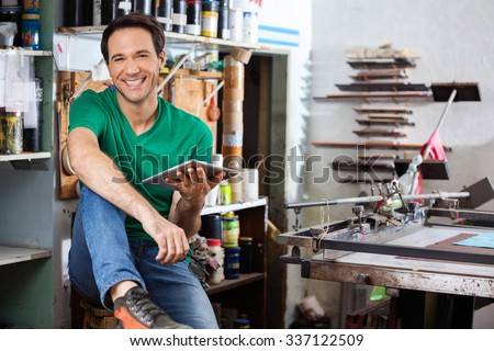 Portrait of confident worker holding digital tablet in paper factory - stock photo