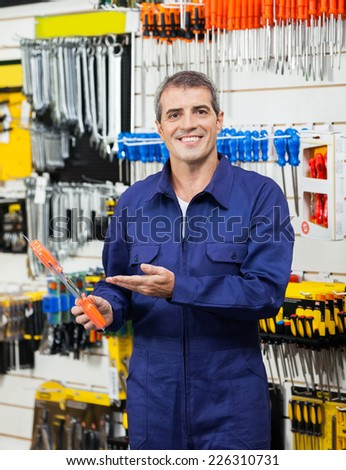 Portrait of confident worker showing packed screwdriver in shop