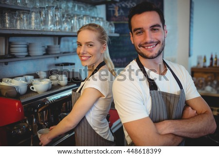 Portrait of confident worker with colleague standing at cafeteria