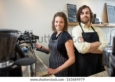 Portrait of confident workers standing at counter in coffeeshop - stock photo