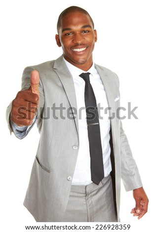 Portrait of confident young African American businessman gesturing thumbs up over white background - stock photo