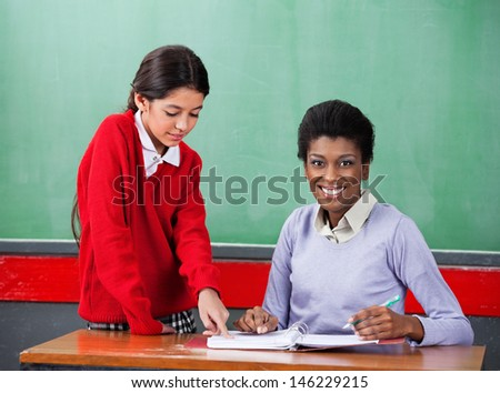 Portrait of confident young African American female teacher with girl pointing on binder at desk in classroom - stock photo