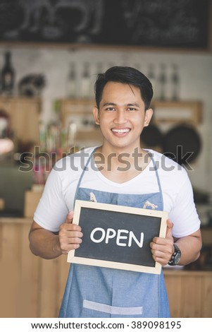 portrait of confident young asian male cafe owner standing with blank board - stock photo