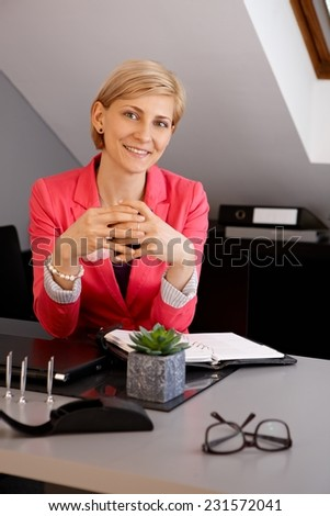 Portrait of confident young blonde businesswoman sitting at desk, smiling. - stock photo