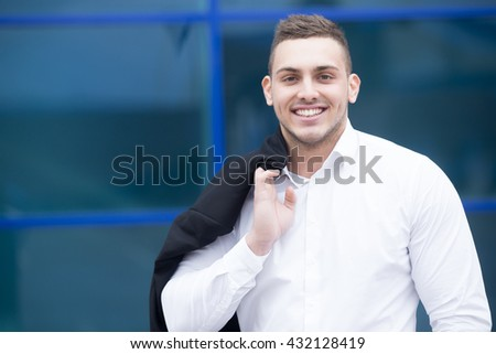 Portrait of confident young business man looking at camera with happy facial expression outdoors. Successful attractive caucasian man posing on the street and smiling - stock photo