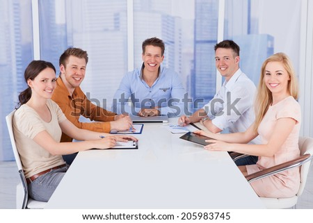 Portrait of confident young business people sitting at conference table in office