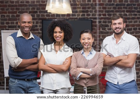 Portrait of confident young business people with arms crossed in office