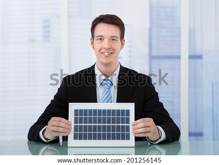 Portrait of confident young businessman holding solar panel at office desk - stock photo