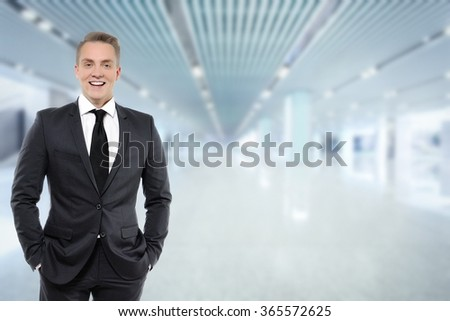 Portrait of confident young businessman in formals smiling. Background of business building.  - stock photo