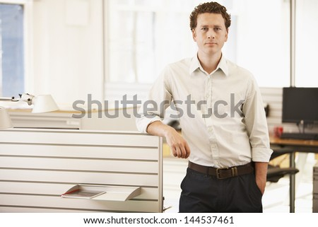 Portrait of confident young businessman standing by cubicle - stock photo