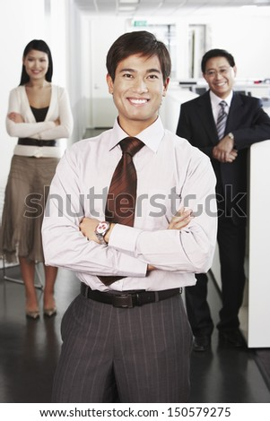 Portrait of confident young businessman standing in front of team in office