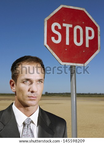 Portrait of confident young businessman standing next to stop sign against blue sky - stock photo