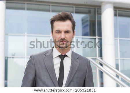 Portrait of confident young businessman standing outside office building - stock photo