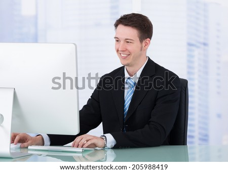 Portrait of confident young businessman using computer at office desk - stock photo