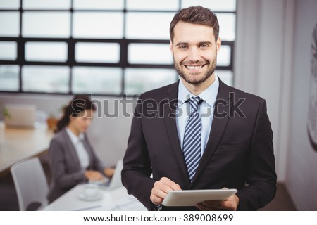 Portrait of confident young businessman using digital tablet while colleague in background - stock photo
