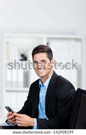 Portrait of confident young businessman using mobile phone in office - stock photo