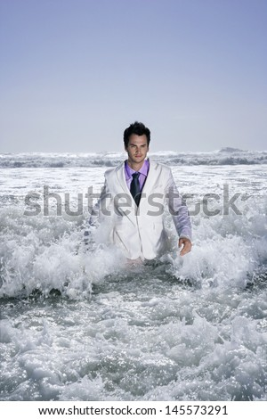 Portrait of confident young businessman walking into sea - stock photo