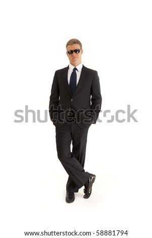Portrait of confident young businessman wearing a suit and sunglasses - stock photo