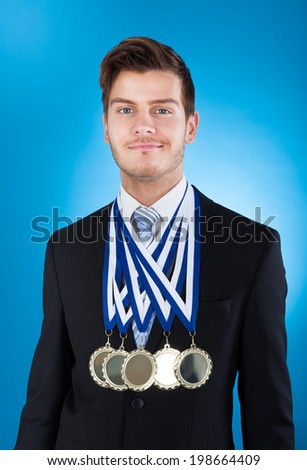 Portrait of confident young businessman wearing medals against blue background - stock photo