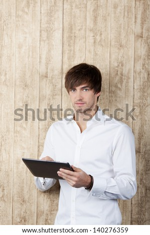 Portrait of confident young businessman with digital tablet standing against wooden wall - stock photo