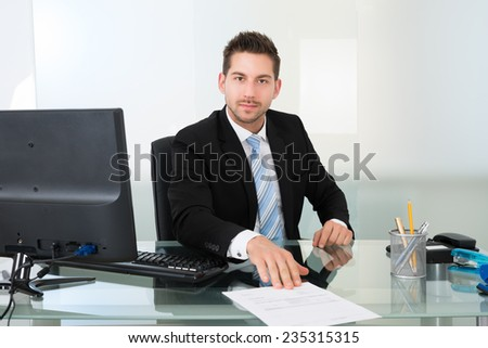 Portrait of confident young businessman with document at desk in office - stock photo