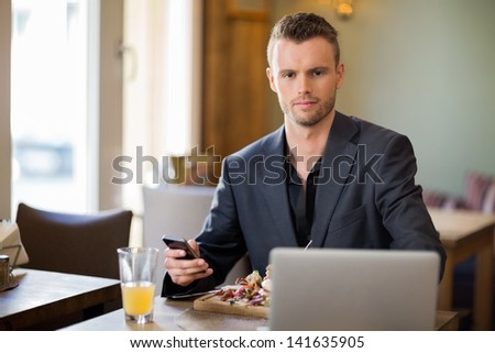Portrait of confident young businessman with mobilephone and laptop sitting in coffeeshop - stock photo
