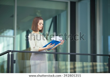 Portrait of confident young businesswoman analyzing paperwork in front of her contemporary office - stock photo