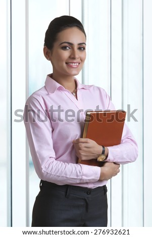 Portrait of confident young businesswoman holding diary in office